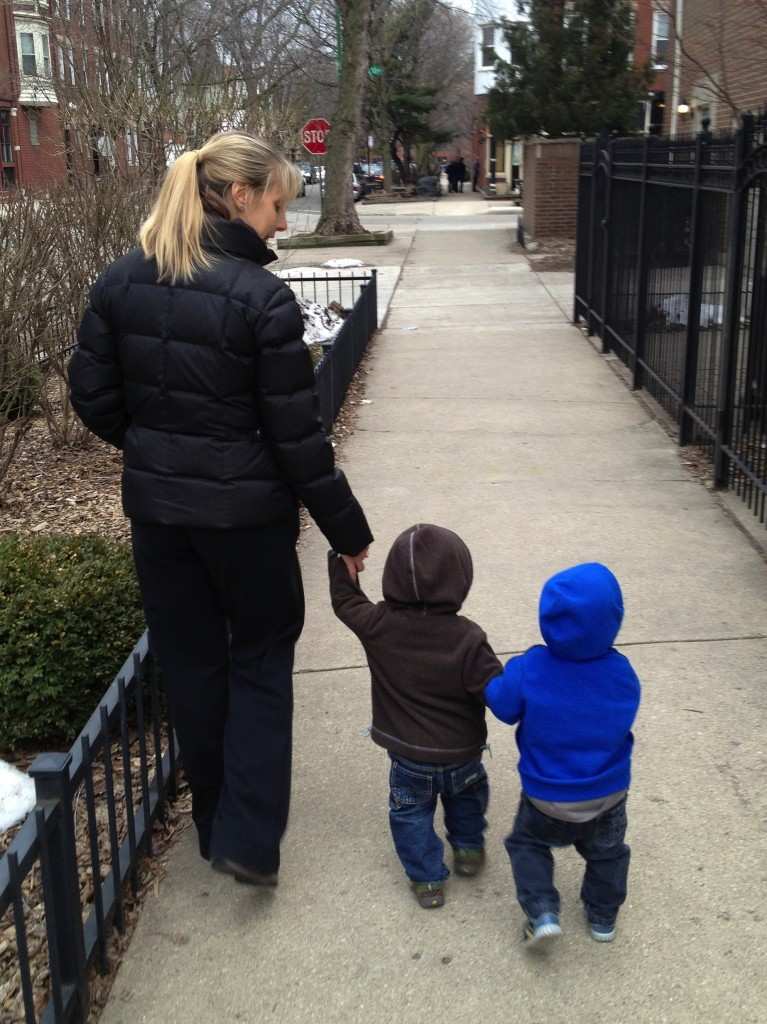 Toddlers holding hands with mom